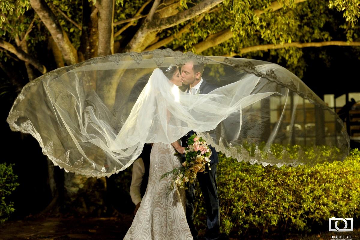 Foto de um casal se beijando enfrente a uma árvore enquanto o véu da noiva está ao ar.