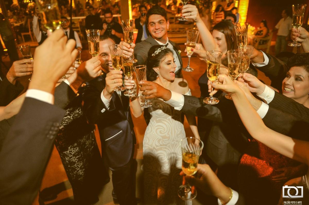 Foto dos noivos e convidados levantando as taças no alto