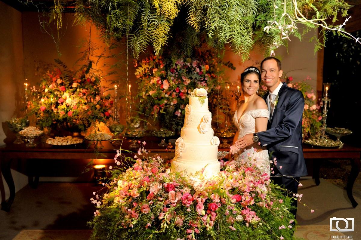 Foto de noivos junto ao seu bolo de casamento.