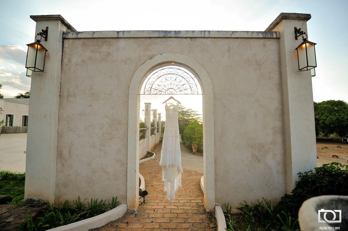 Foto de um vestido de noiva espendurado em um portal.