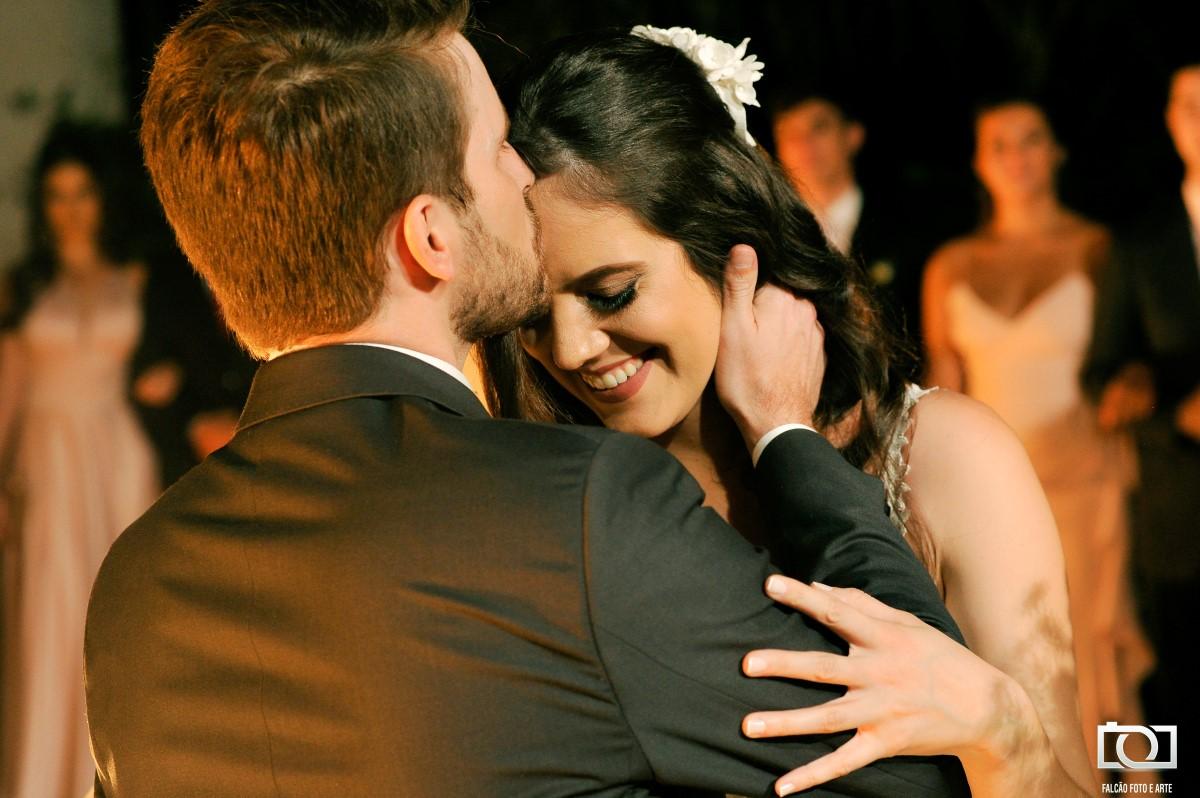 Foto de um noivo beijando sua noiva na testa durante seu casamento.