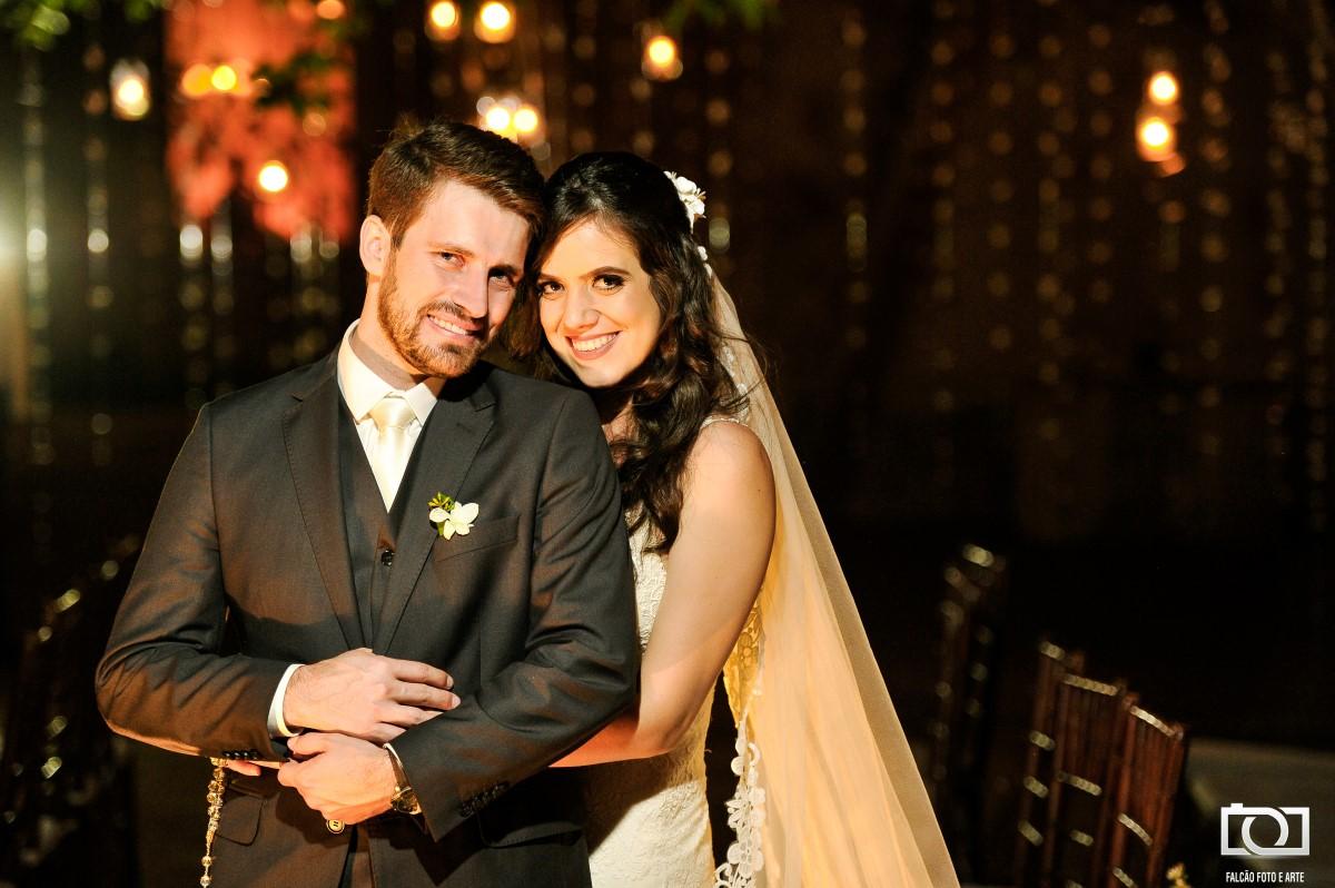Foto de uma noiva segurando seu noivo pela cintura após seu casamento.