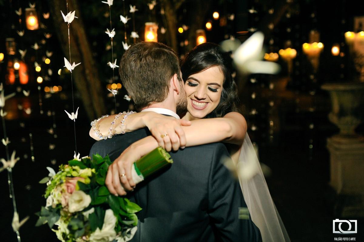 Foto de um noivo beijando sua noiva enquanto estão abraçados com vários origamis espendurados