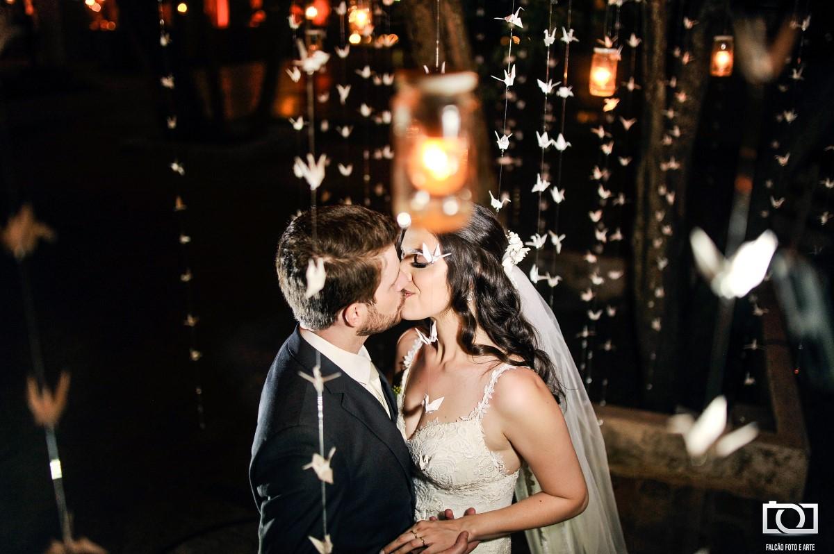 Foto de um casal de noivos se beijando e abraçados com vários origamis espendurados