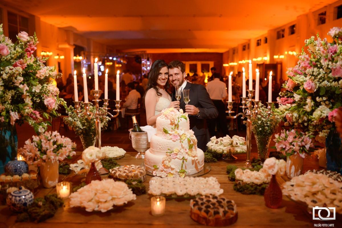 Foto de um casal de noivos abraçados e segurando taças de champagne em frente ao seu bolo de casamento.