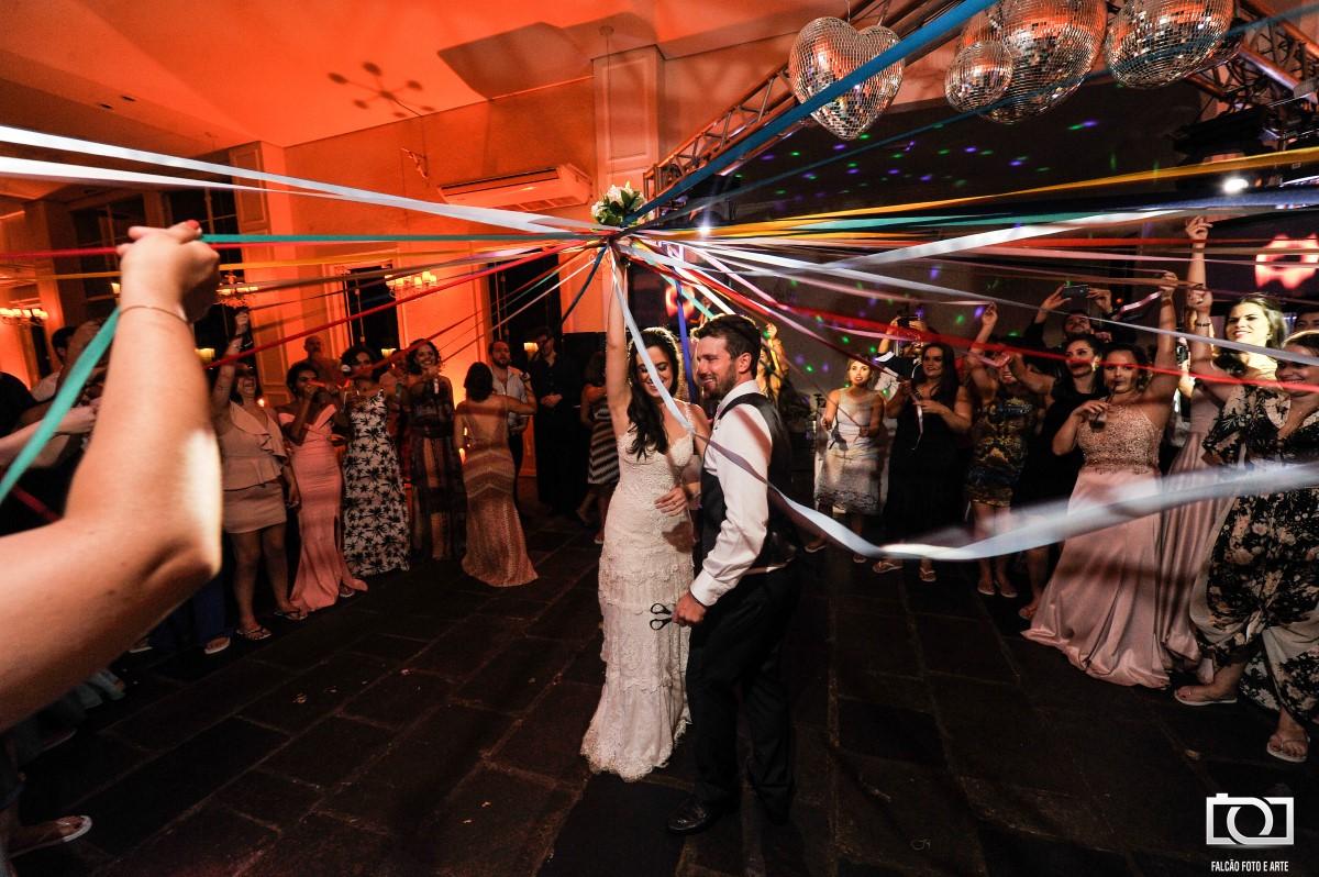 Foto de um casal e convidados segurando várias faixas de diversas cores diferentes durante a festa de casamento..