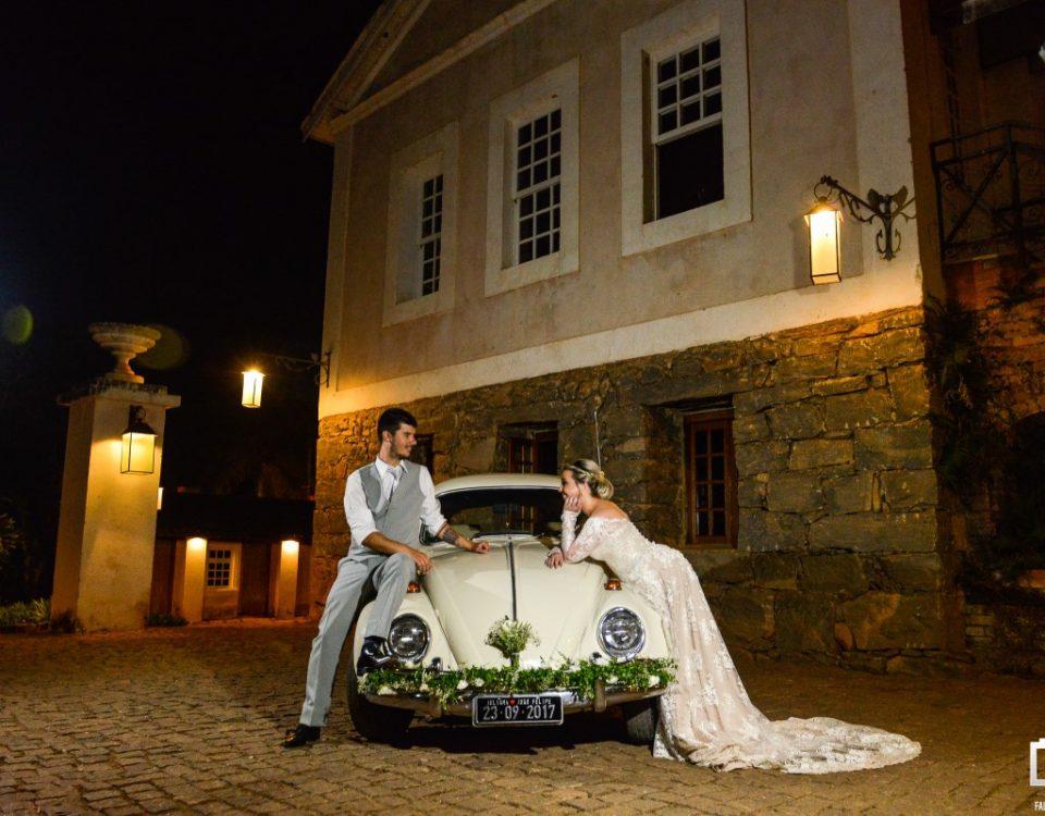Foto de noivos apoiados em um carro e se olhando.