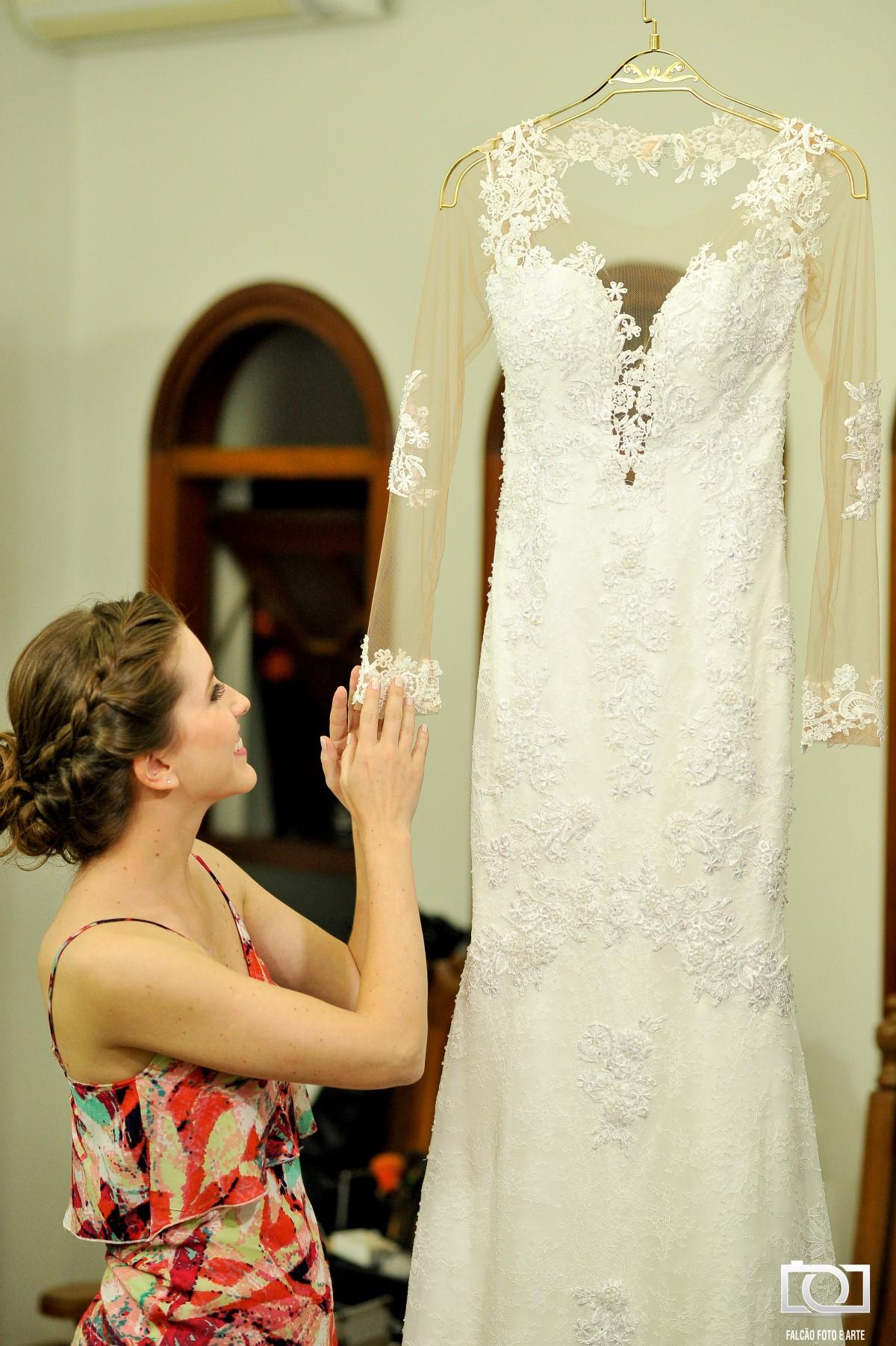 Foto de uma noiva segurando a manga de seu vestido que está espendurado.