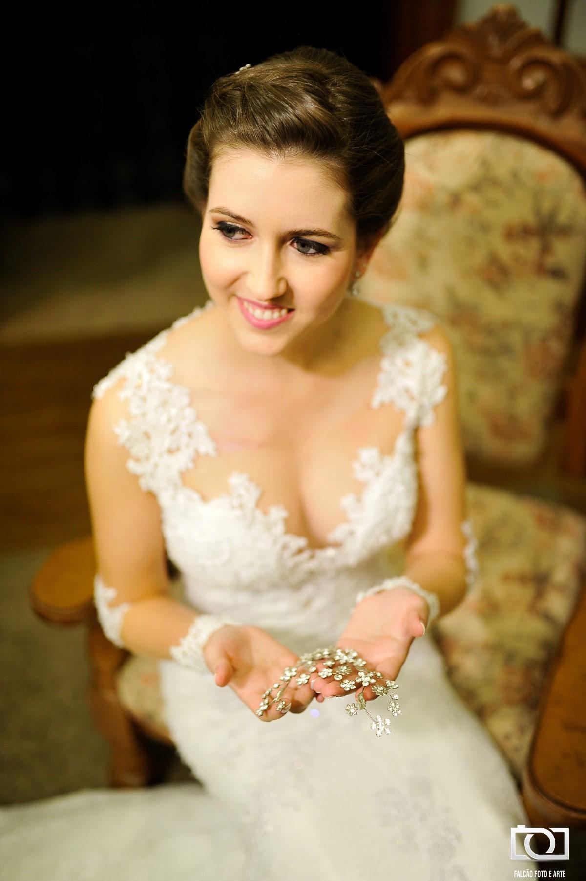 Foto de uma noiva segurando o enfeite que irá no seu cabelo.