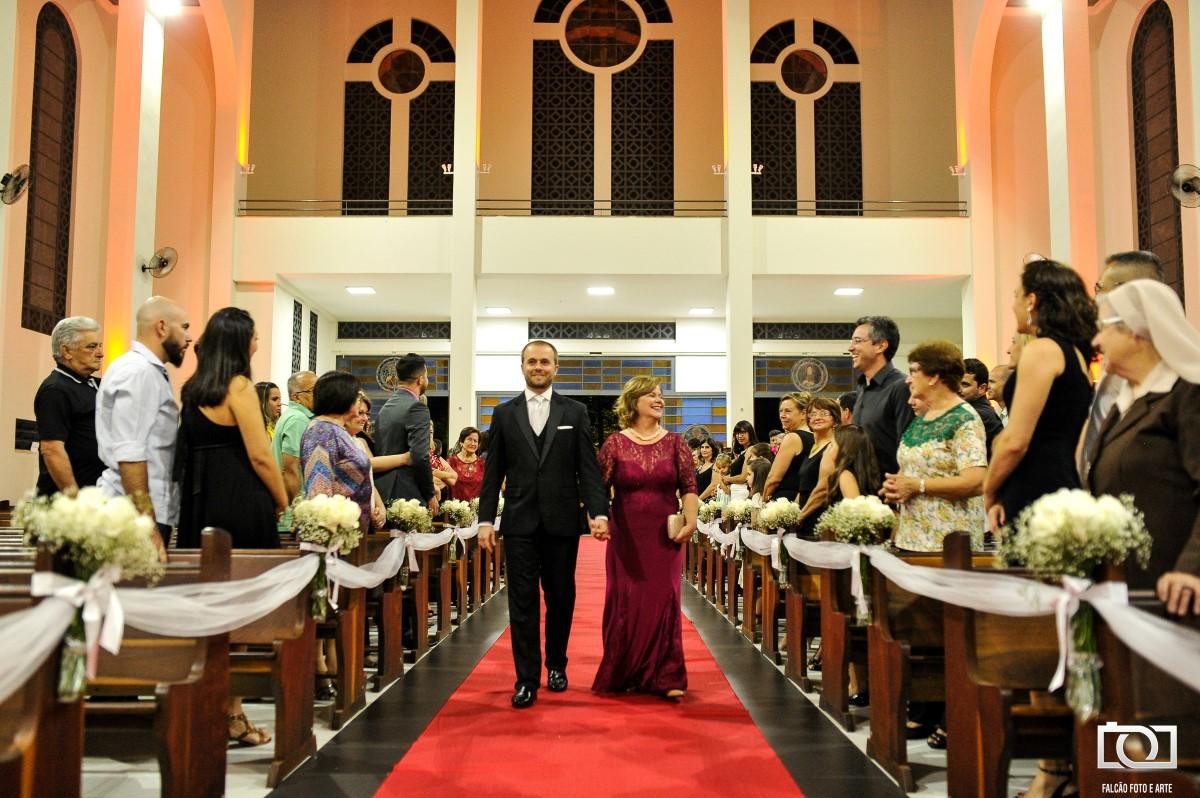 Foto de um noivo entrando com sua mãe pela igreja até o altar.