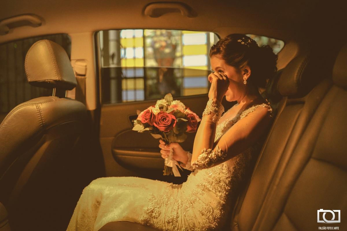 Foto de uma noiva segurando seu buquê dentro do carro.