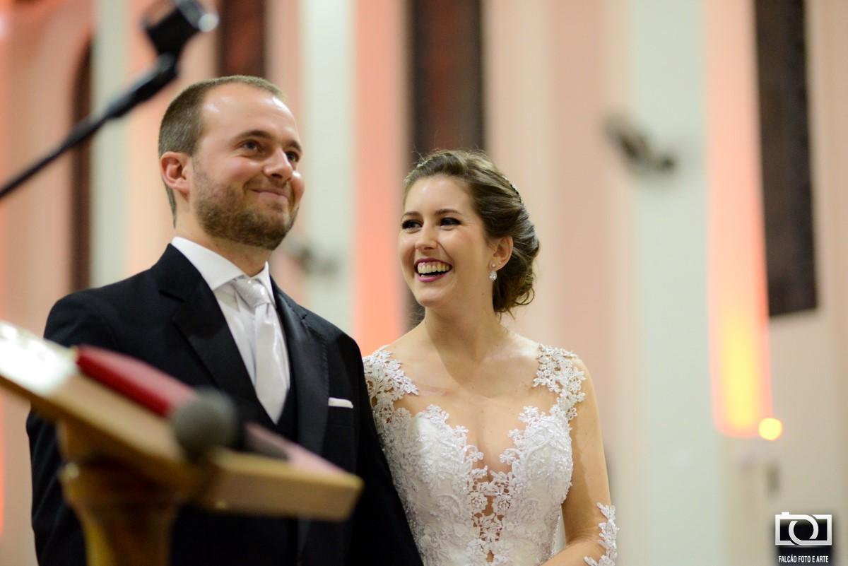 Foto de um casal sorrindo em sua cerimônia de casamento.