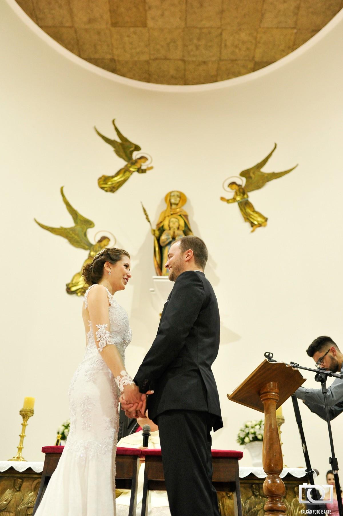 Foto de noivos sorrindo em frente ao altar em sua cerimônia de casamento.