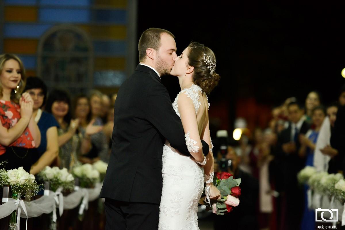 Foto dos noivos se beijando durante a cerimônia de seu casamento.