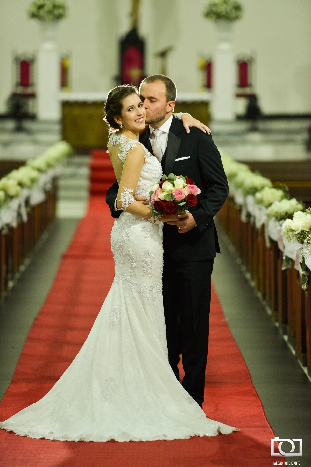 Foto de um casal recém-casados abraçados na igreja enquanto o marido beija a esposa.
