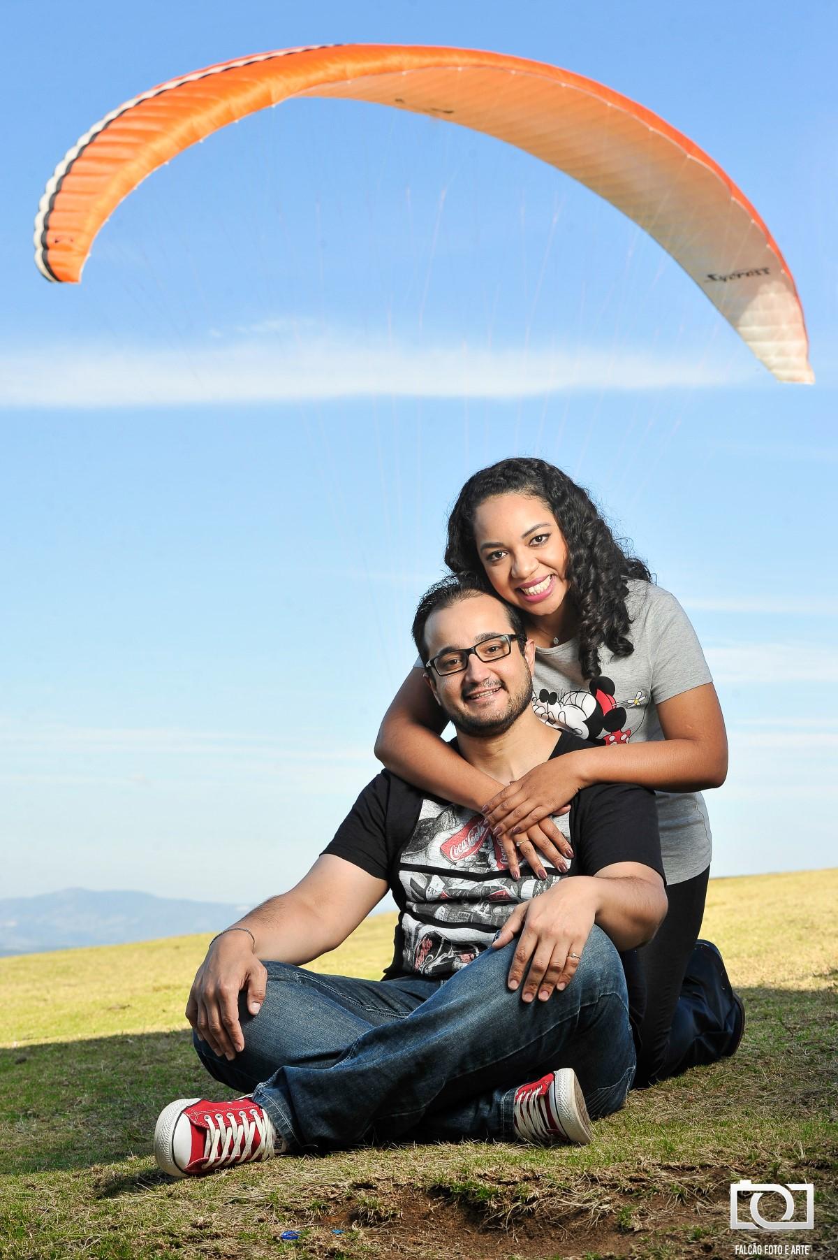 Foto de um noivo sentado na grama com a sua noiva ajoelhada e o abraçando pelas costas.