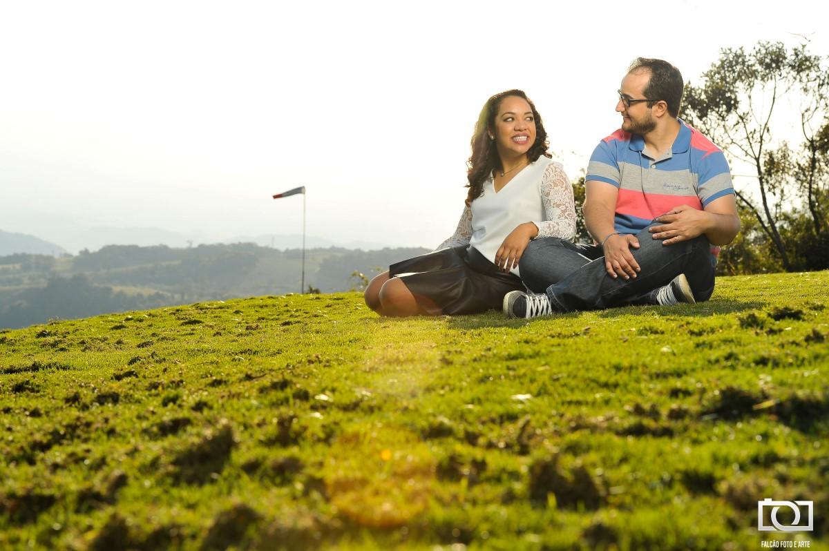 Foto de um casal sentados em um gramado e se olhando.