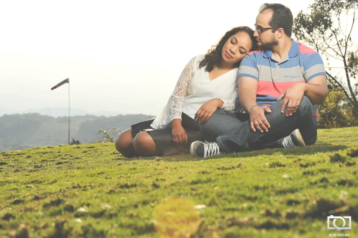 Foto de uma noiva apoiando a cabeça no ombro se seu noivo enquanto estão sentados em um gramado.