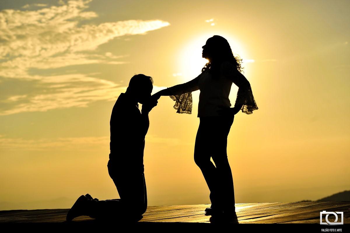 Foto de um noivo beijando a mão de sua noiva durante um por do sol.