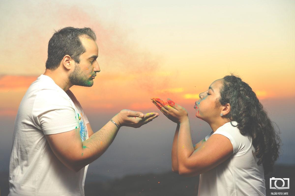 Foto de um casal assoprando pó colorido.