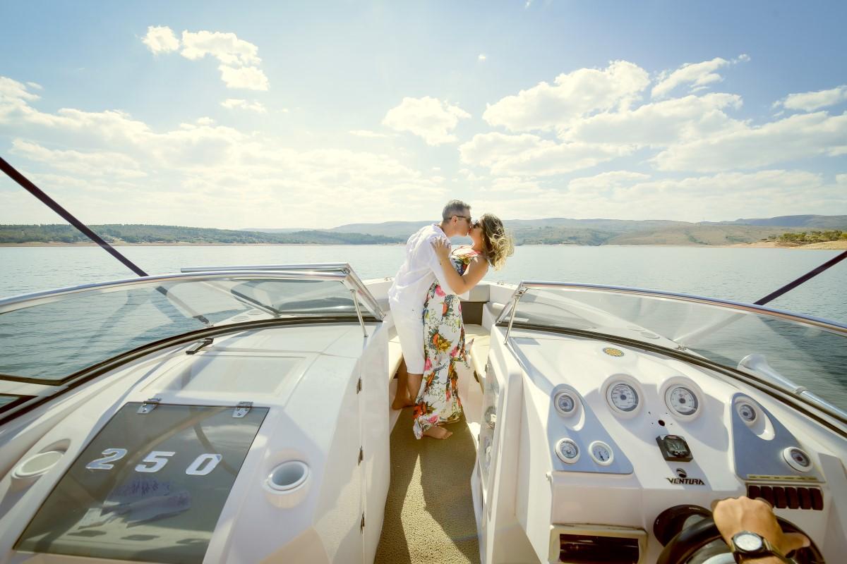 Foto de um casal se beijando dentro de uma lancha.