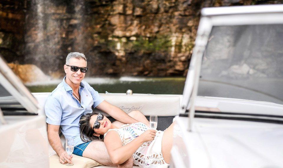 Foto de uma noiva deitada no colo de seu noivo com uma cachoeira ao fundo.