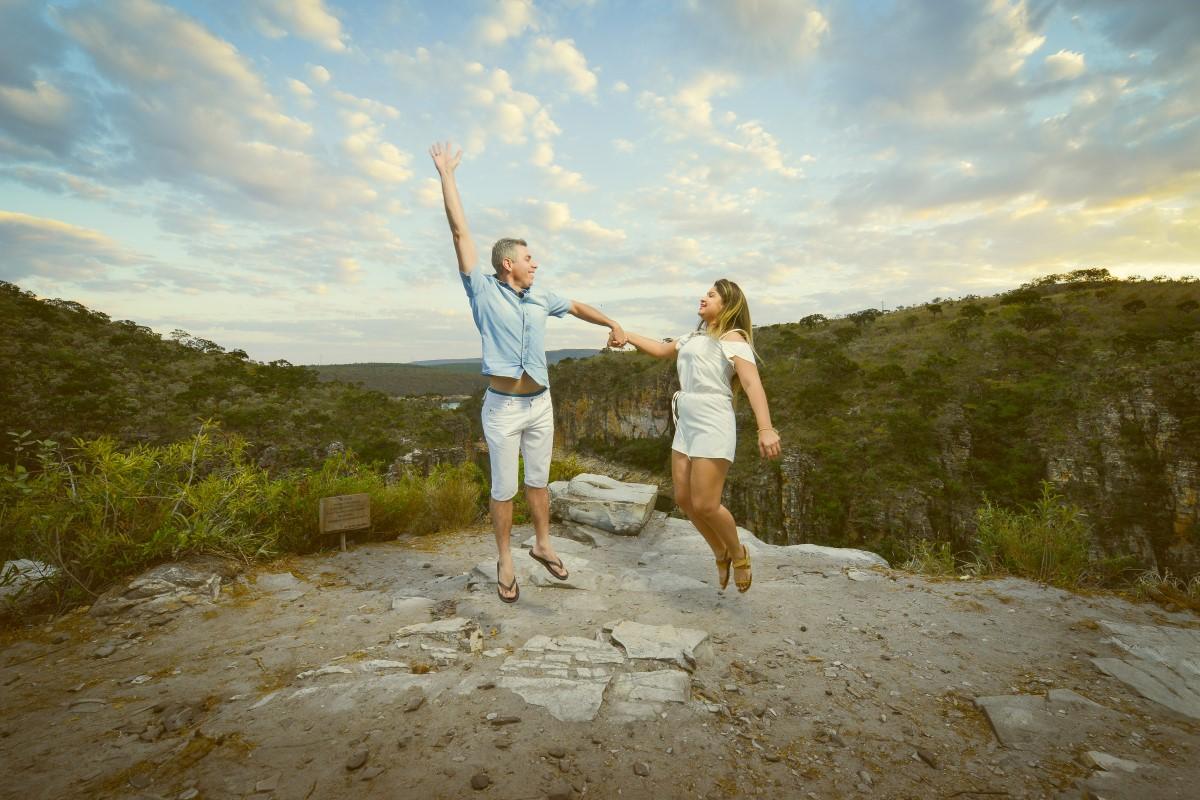 Foto de um casal pulando de mãos dadas com um pôr do sol ao fundo.