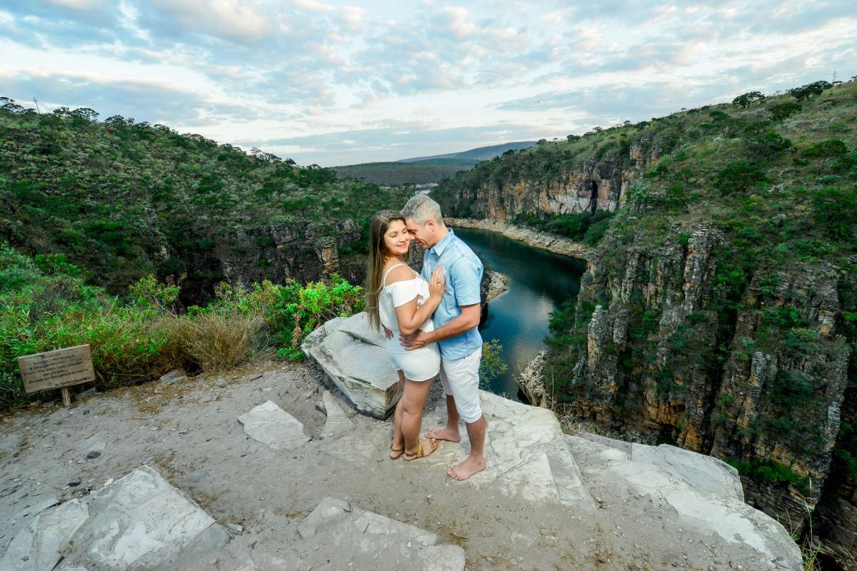 Foto de um casal se abraçando com um cânion de fundo.