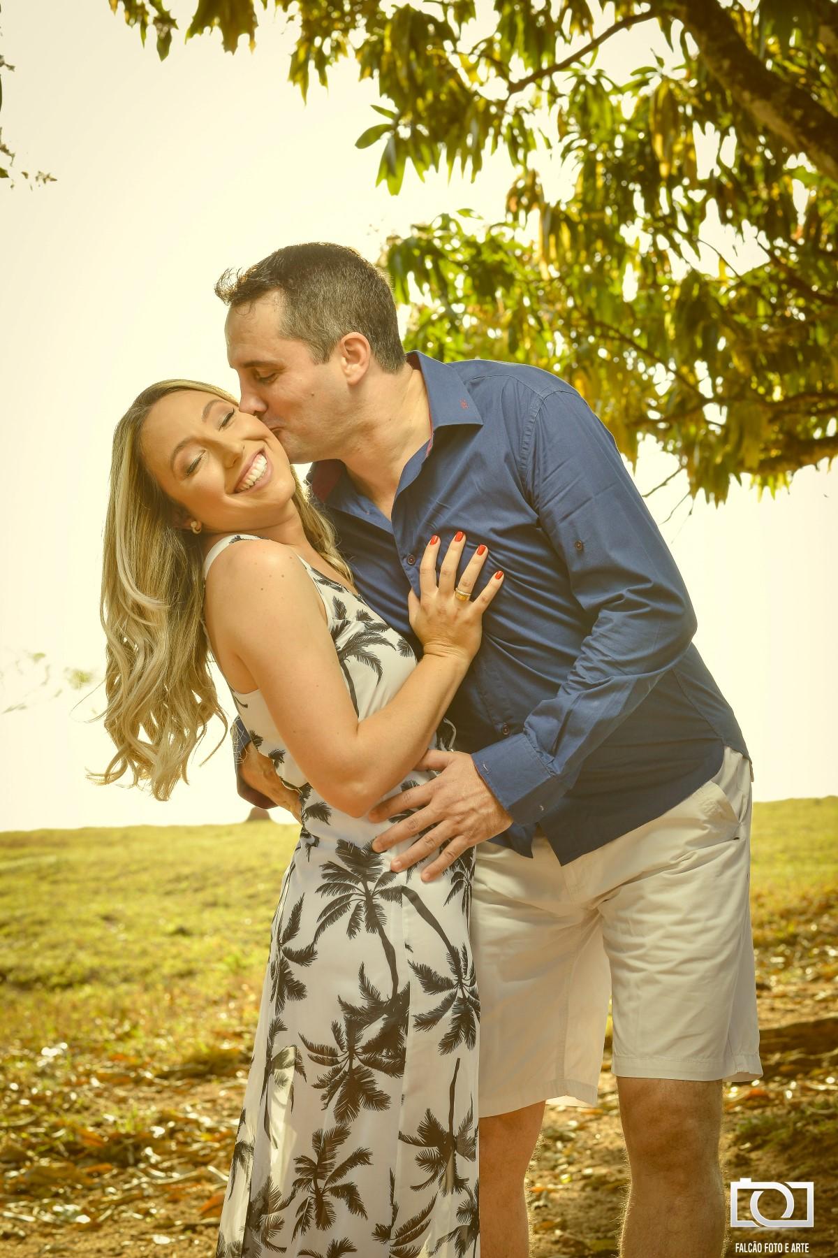 Foto de um noivo beijando sua noiva no rosto enquanto a segura pela cintura.