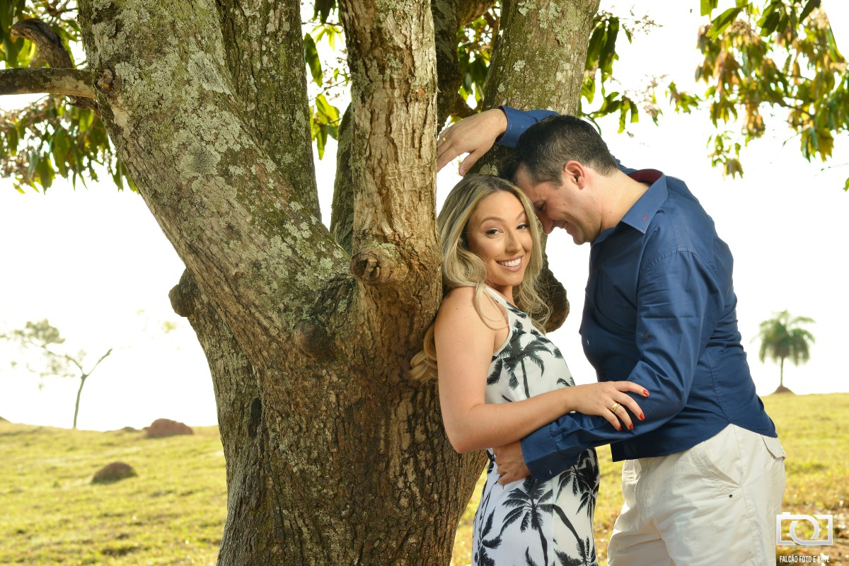 Foto de um casal encostados em uma árvore.