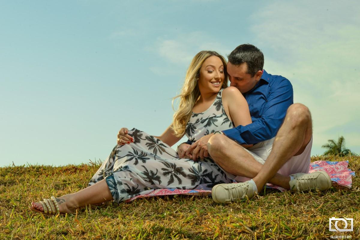 Foto de um casal sentados em um gramado enquanto o noivo beija ela no ombro.