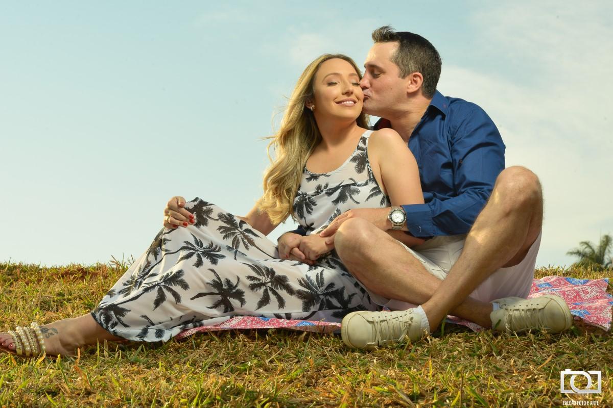 Foto de um casal sentados em um gramado enquanto o noivo beija ela no rosto.