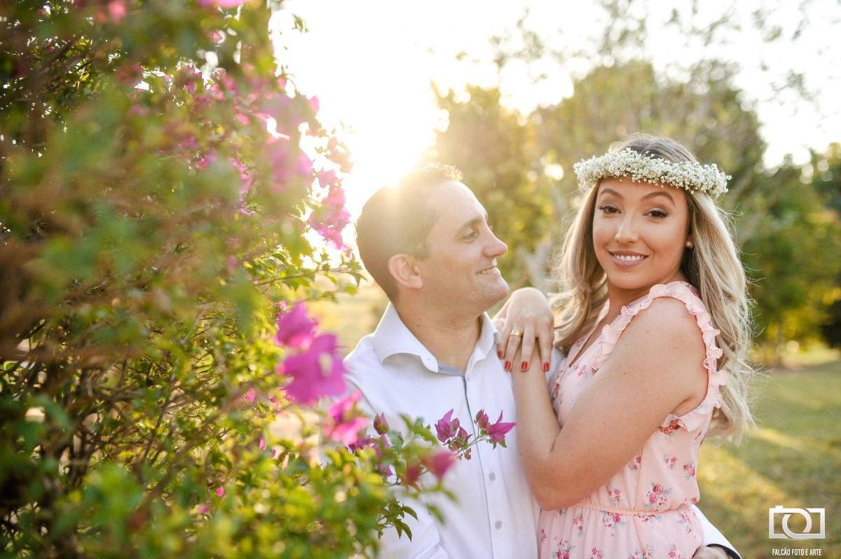 Foto de um casal abraçados com uma árvore de flores rosas ao lado.