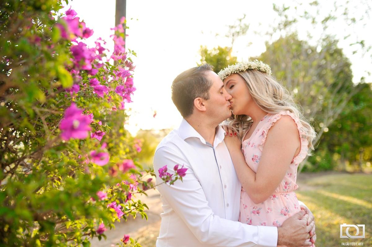 Foto de um casal se beijando com uma árvore de flores rosas ao lado.