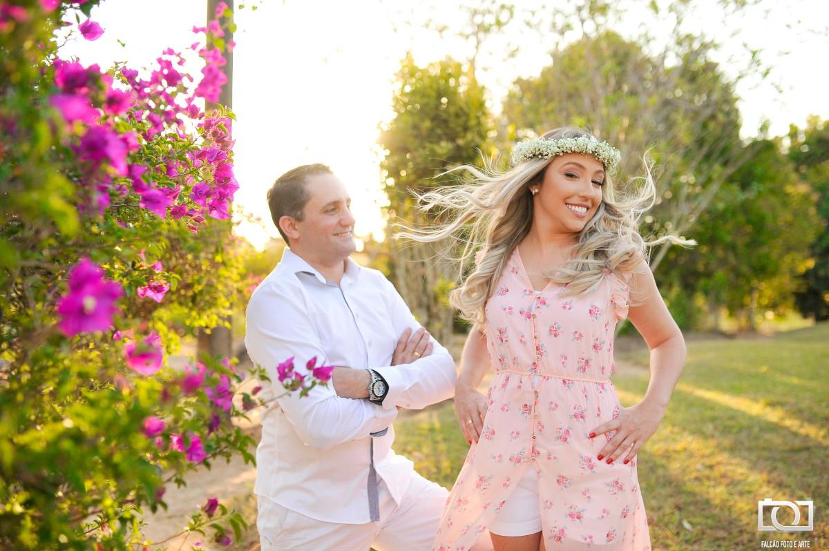 Foto de um noivo observando sua noiva com uma árvore de flores rosas ao lado.