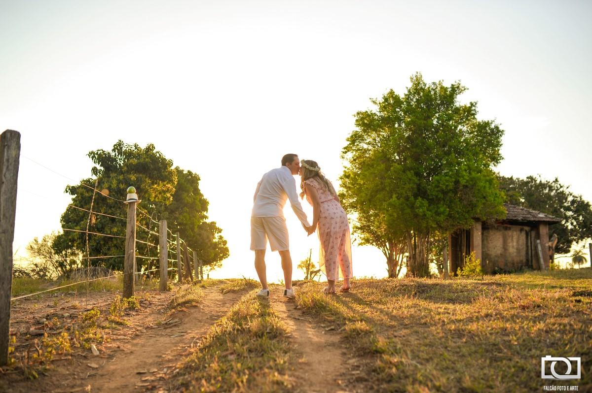 Foto de um casal se beijando em uma estrada com um pôr do sol ao fundo.