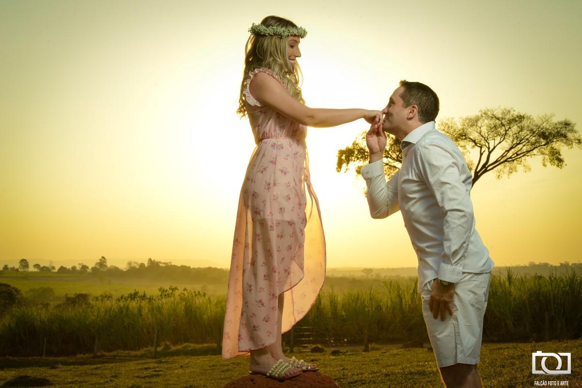 Foto de um noivo beijando a mão de sua noiva com um pôr do sol ao fundo.