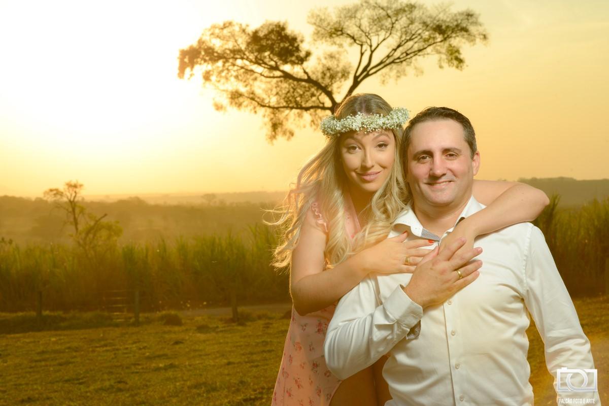 Foto de uma noiva abraçando seu noivo pelas costas durante um pôr do sol.