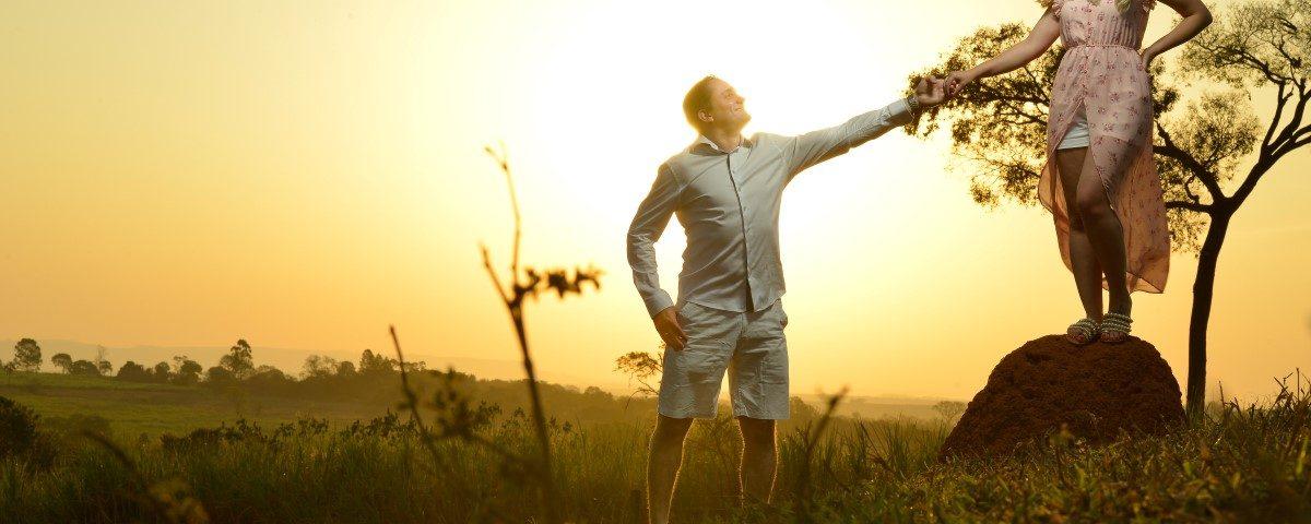 Foto de um noivo segurando a mão de sua noiva que está em cima de um cupinzeiro durante um pôr do sol.