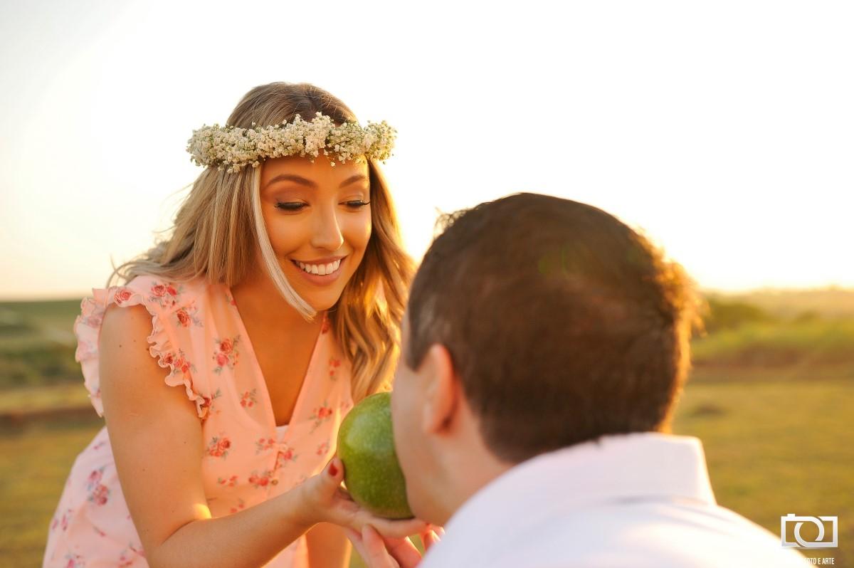 Foto de um noivo beijando um fruto segurado por sua noiva.