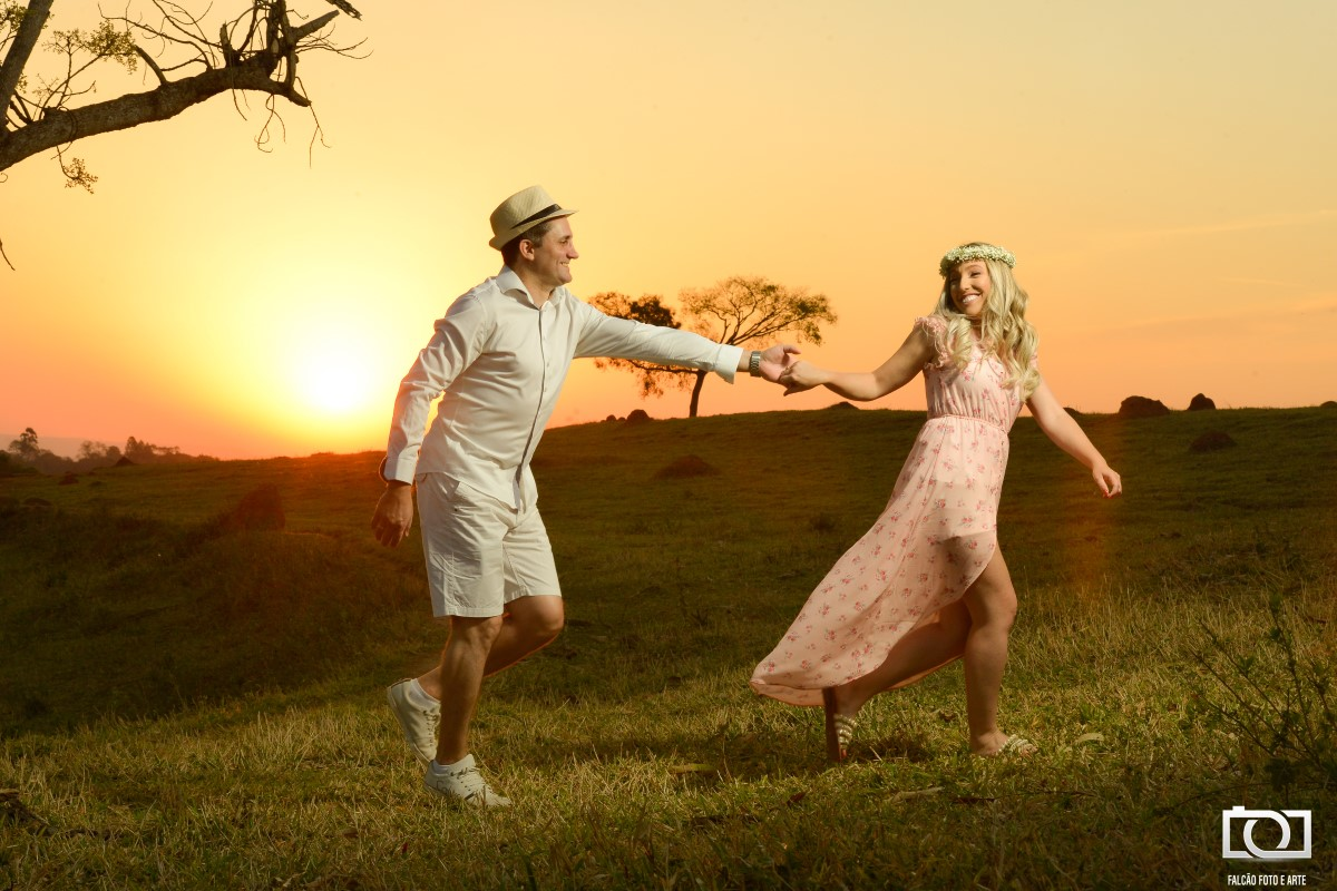 Foto de um casal correndo de mãos dadas durante um pôr do sol.
