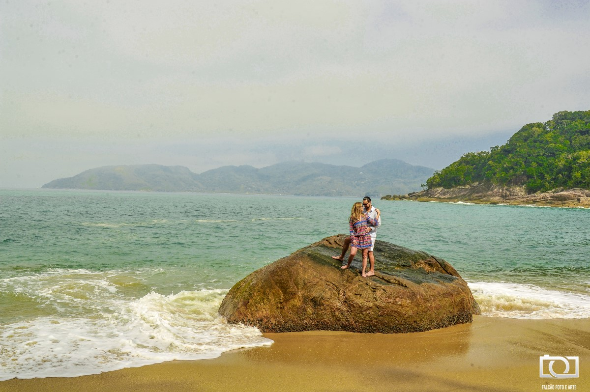 Foto de um casal em cima de uma pedra com o mar ao fundo.