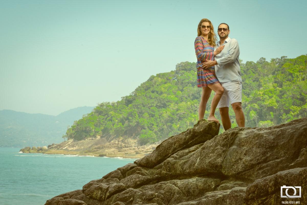 Foto de um casal em cima de uma pedra com o mar e uma floresta ao fundo.
