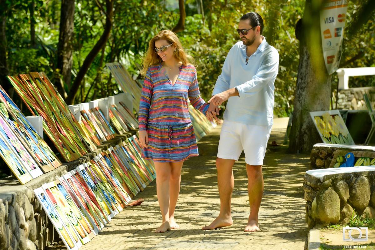 Foto de um casal observando obras de arte expostas na calçada.