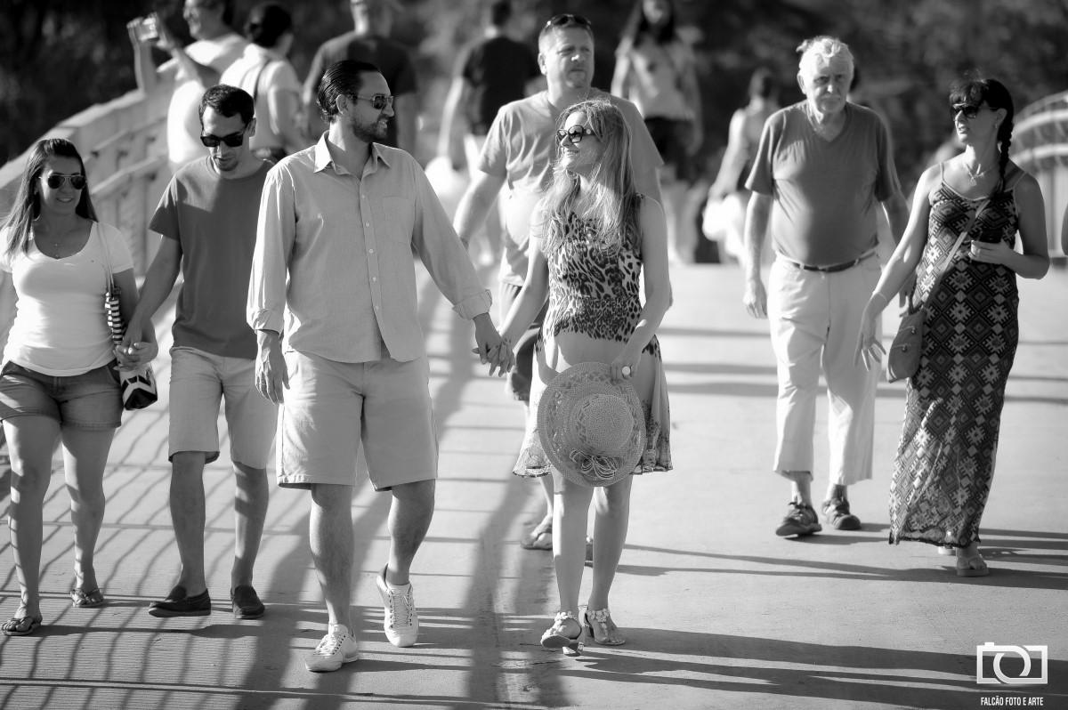 Foto de um casal andando de mãos dadas com várias pessoas ao redor.