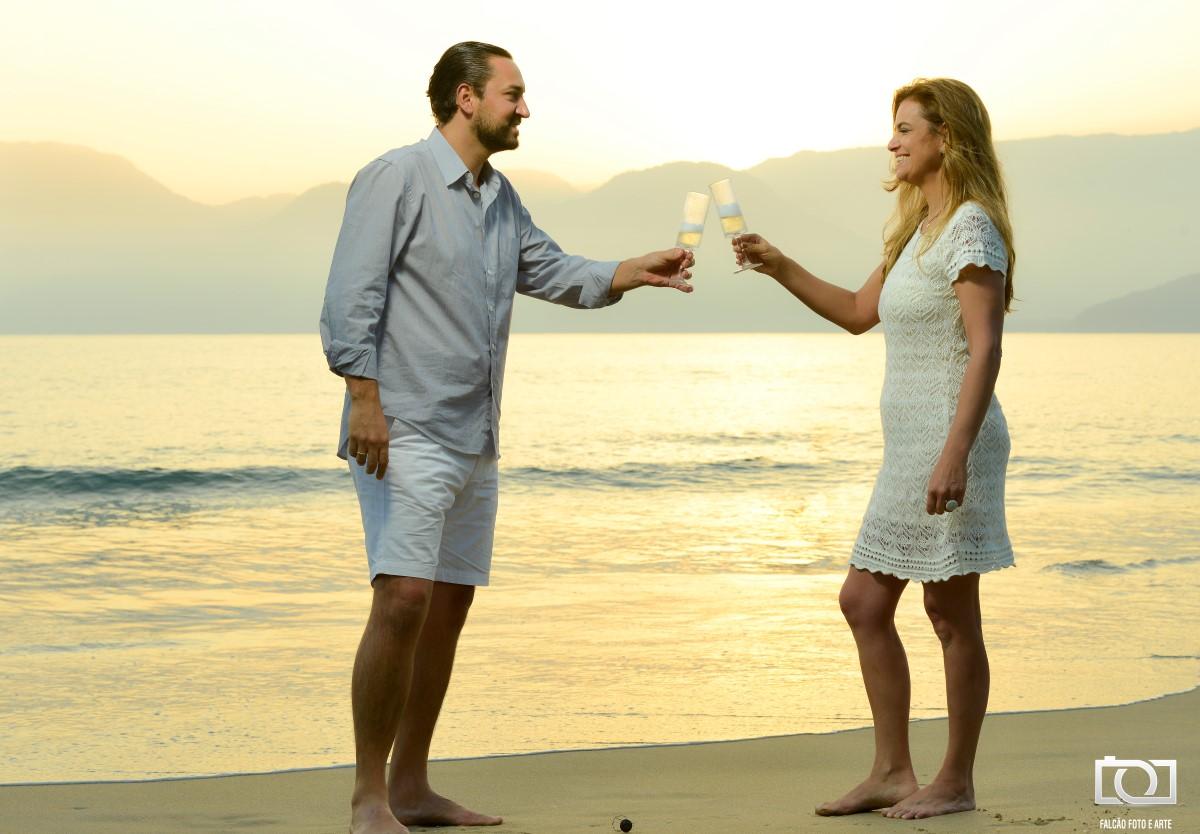 Foto de um casal brindando na praia durante um pôr do sol.