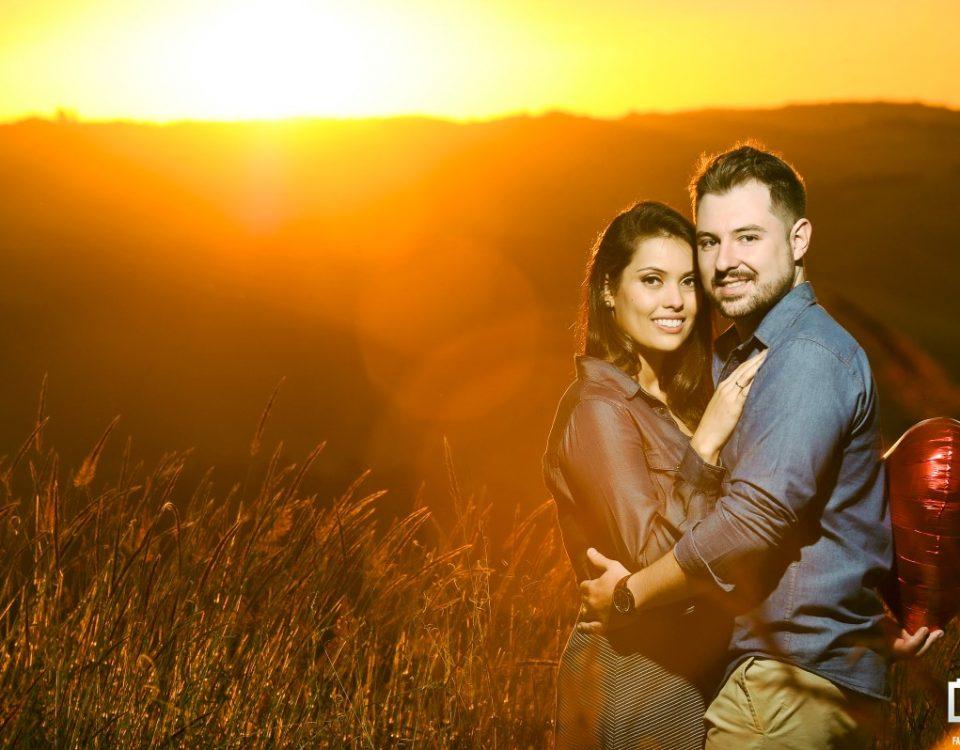 Foto de um casal de noivos abraçados e segurando um balão vermelho em forma de coração com um por do sol ao fundo.